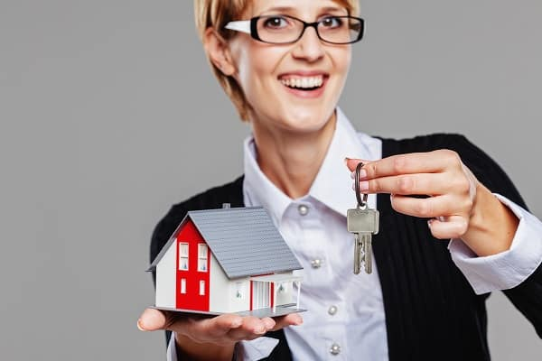 Attractive Female Real Estate Agent Presenting A Detached House Model And Keys Isolated On Grey